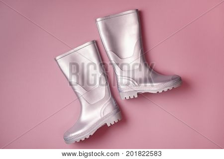 From above shot of trendy silver rain boots on pink background. Top view. Flat lay