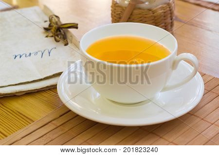 Herbal tea in the white cup with saucer on the bamboo napkin on a blurred background of a menu in retro cafe