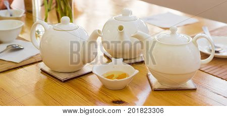 Panorama of the three white teapot on a ceramic trivets on a wooden table on a background of a tea appliances