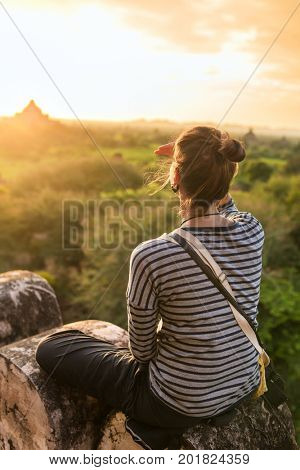 Young woman watching  sunrise in Bagan, Myanmar.