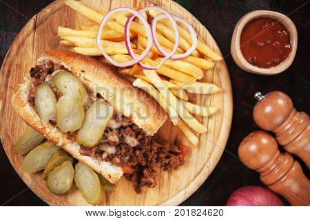 Sloppy joes, ground beef sandwich with pickles and french fries