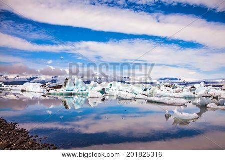 The procession of luminous icebergs on Jokulsarlon, Iceland. The concept of extreme northern tourism. Striped clouds beautifully reflected in the smooth water of lagoon