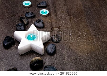 Turquoise Candles In White Star Candle Holder On Gray Slate Background With Water Droplets