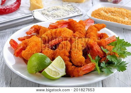 light and crispy crunchy parmesan bread crumbs coating Fried Shrimps on white plate on wooden table with bread crumbs parmesan cheese grater garlic on background view from above close-up