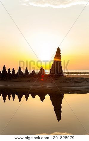 Beach with sandcastles on spectacular Baltic sea sunset background in Latvia. Multicolored summertime outdoors vertical image. Copy space.