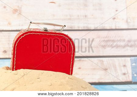 Vintage red suitcase in sand at the beach