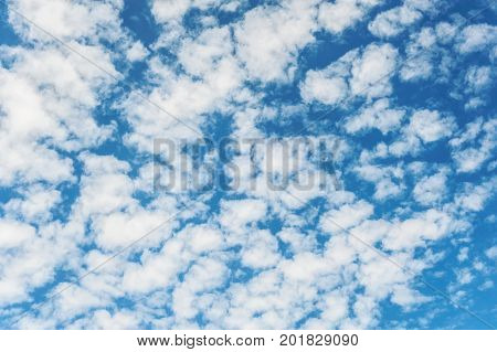 White clouds on blue sky background. Vibrant outdoors horizontal image with copy space.
