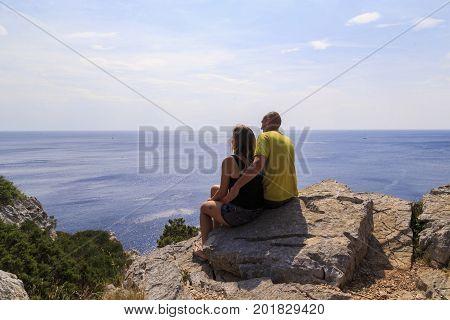 DUGI OTOK, CROATIA - SEPTEMBER 7, 2016: Unknown couple sits on steep coastal cliffs of the island in Telascica Nature Park.