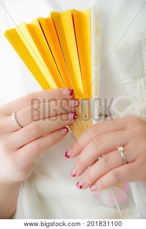 Traditional Japanese ceremony wedding lovely day, young married bride wear kimono, holding golden paper fan hands in white background