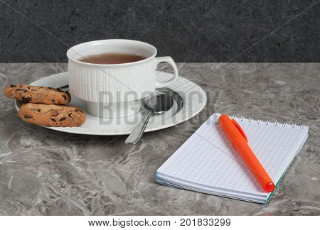 Breakfast with tea cup, biscuits, notebook and a pen  on a gray marble countertop