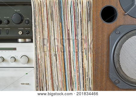 Retro receiver, amplifier, turntable and stack of old vinyl records near the big wooden sound speaker