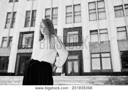 Portrait Of A Fabulous Young Successful Woman In White Blouse And Broad Black Pants Posing On The St