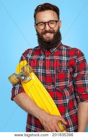 Young hipster man in glasses and checkered shirt holding yellow cruiser board and keeping eyes closed.