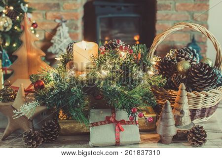 Cosy Christmas composition, presents and decorations on the table in front of the fireplace with woodburner, lit up Christmas tree with baubles and ornaments and garlands, selective focus, toned