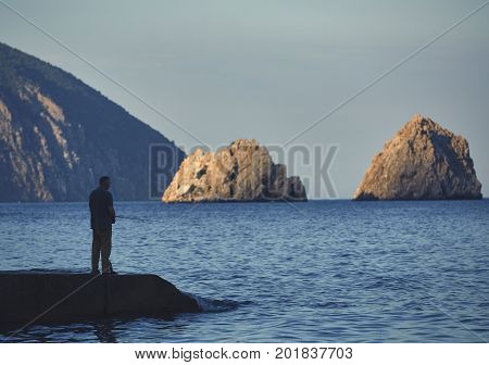Side view of male fisherman standing on a pier with a fishing rod at sunset
