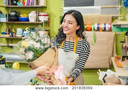 Female florist offering flowers at the counter in the florist shop
