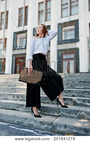 Portrait Of A Flawless Young Woman In White Blouse, Wide Black Pants And Classic High Heels Posing O