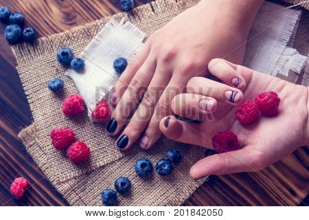 bog whortleberry raspberries and female hands with black and pink art manicure on a sackcloth and wooden background