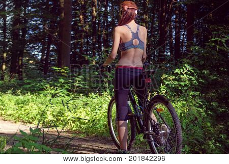 Girl cyclist on a mountain bike in a green forest