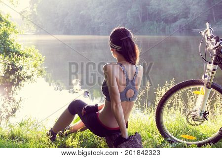 Girl cyclist with a mountain bike sits near the river