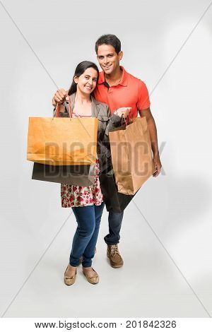 Indian happy and Young couple with shopping bags, asian man and women holding shopping bags, isolated over white background