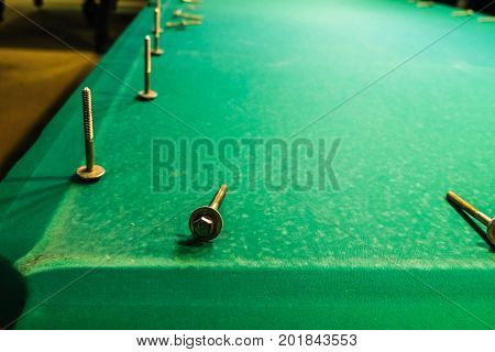 the bolts are on the green baize of the billiard table