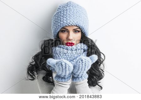 Beautiful woman in blue winter hat, scarf and mittens blowing on palms