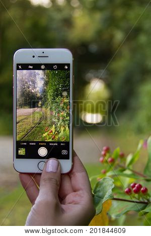 Manchester United Kingdom - 4 August 2017: Woman hand takung photo using mobile phone of train lines in nature surroundings at Heaton Park Manchester
