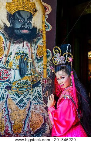 Chachoengsao, Thailand - July 14, 2013 : Beautiful woman with traditional chinese pink dress at Chinese shrine door with painting of ancient soldier in Thailand.