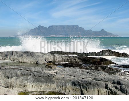 FROM CAPE TOWN, SOUTH AFRICA, WITH TABLE MOUNTAIN IN THE BACK GROUND, AND WAVES WASHING OVER SOME ROCKS IN THE FORE GROUND