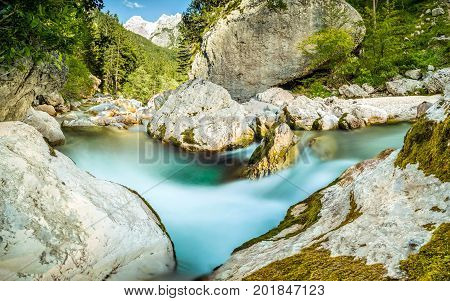 Natural wild river with turquoise water rapids in forest mountain valley. Soca River, Slovenia.
