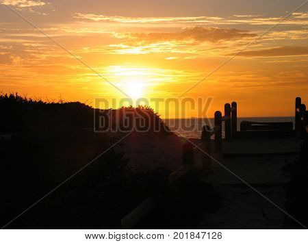A SILHOUETTE IN THE FORE GROUND, WITH THE GOLDEN RAYS OF THE SUN SETTING IN THE BACK GROUND