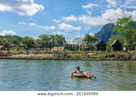 Vang Vieng, Laos - January 19, 2017: Unidentified tourist enjoy tubing in Song River in Vang Viang village, Laos.