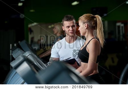 Young male fitness coach with beautiful female client on treadmill machine. Cute blonde woman working out in gym with personal trainer.Healthy lifestyle, fitness and sports concept.