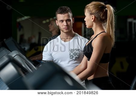 Cute blonde woman working out in gym with the assistance of fitness coach. Young male personal trainer with female client on treadmill. Healthy lifestyle, fitness and sports concept.