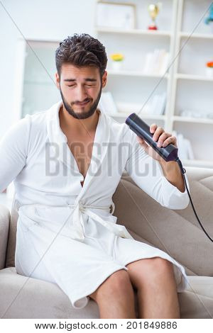 Young man drying hair at home with a hair dryer blower