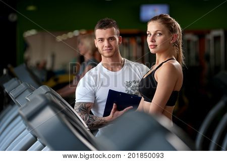 Happy smiling young woman and her fitness coach standing together on treadmill zone and looking at the camera. Male personal trainer standing with clipboard. Healthy lifestyle, fitness concept.