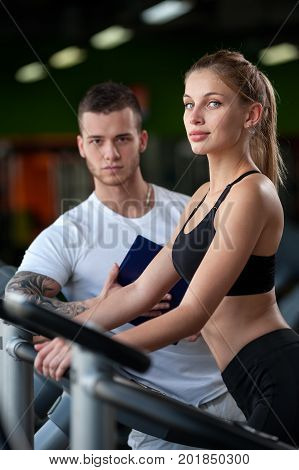 Closeup of blonde female working out on elliptical machine with the assistance of personal trainer. Healthy lifestyle, fitness and sports concept.Focus on woman