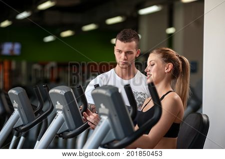 Attractive blonde woman working out with personal trainer in modern fitness center. Young male coach with female client on cardio machine. Healthy lifestyle, fitness and sports concept.