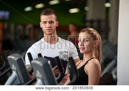 Personal trainer helping his female client on machine. Attractive blonde woman working out in gym with the assistance of fitness coach. Healthy lifestyle, fitness concept.