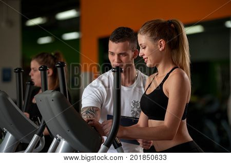 Happy attractive blonde woman working out on elliptical machine with the assistance of personal coach. Healthy lifestyle, fitness concept.