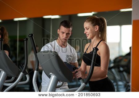 Personal trainer working with female client in gym. Cute blonde woman and coach in fitness center. Healthy lifestyle, fitness concept.