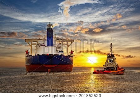 Tanker and tugboat on sea at sunset.