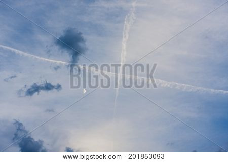 Cross of aircrafts in blue sky with moon and dark clouds