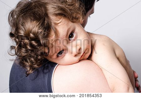 Father holding a cute sick baby boy. Adorable upset child with spots on his face and body form illness mosquito bites roseola rubella measles resting on his parent shoulder.