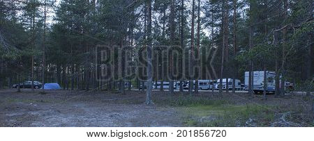 LOMA-KOLI CAMPING ON JULY 04. View of the camping past midnight among the pine trees on July 04, 2017 in Loma-Koli, Karelia, Finland. Caravans, campers and tent. Editorial use.