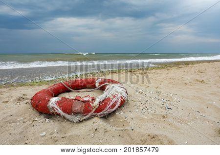Old damaged red lifebuoy on sand .