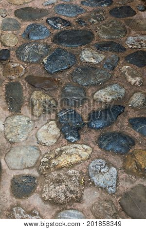 An ancient stone road from cobblestones. Masonry of old stones and bricks. Beautiful unusual background.