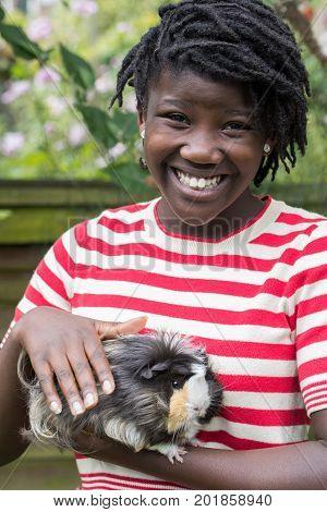 Portrait Of Girl In Garden Looking After Pet Guinea Pig