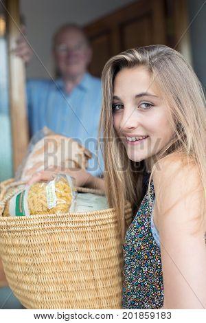 Portrait Of Teenage Girl Doing Shopping For Senior Man